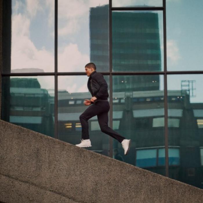 Sharply dressed man running in an urban skyscraper landscape
